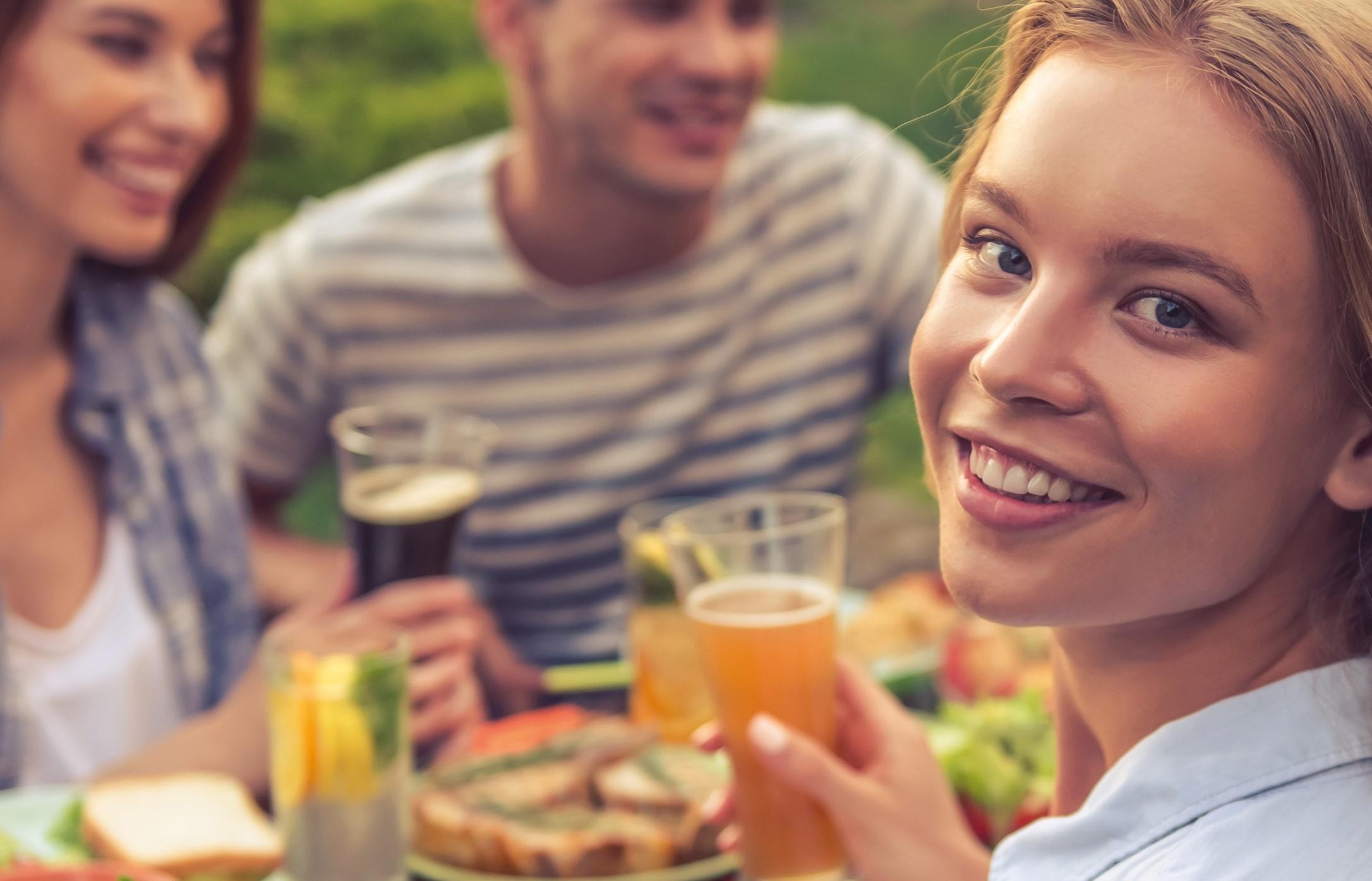 Frau die genießt sitzt bei einem Tisch vollgestellt mit Köstlichkeiten